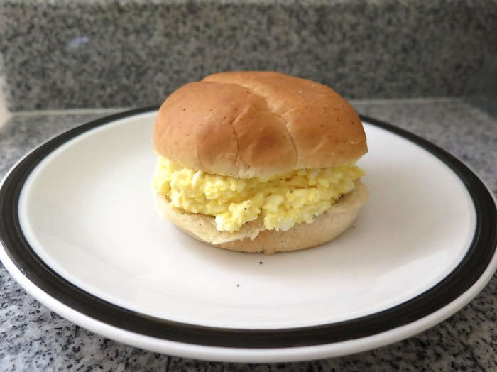 A hamburger bun, generously filled with egg salad