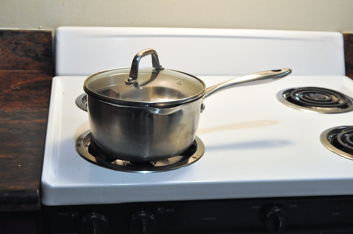 A pot with its handle facing inward as it warms on the stove